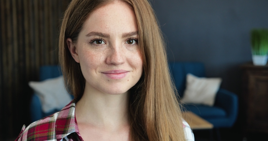 Close Up Portrait of amazing Freckles Girl with Red Hair and Long Eyelashes. Attractive Woman is looking directly at the camera. Having casual Outfit. Positive Emotions. Amazing naturally Faces.