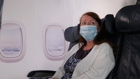 4K: Female Caucasian Airplane Passenger flying wearing a Face mask on plane journey. Air Travel. Stock Video Clip Footage