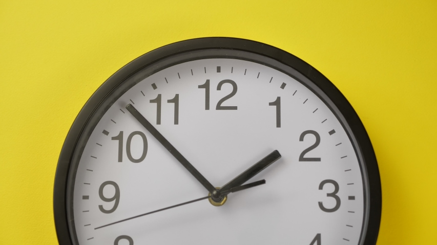 Office Clock Hanging on a Yellow Color Wall