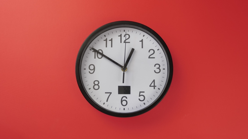 White office clock hanging on a red color wall