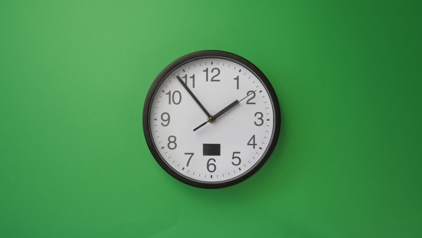 Single white office clock hanging on green background, timelapse