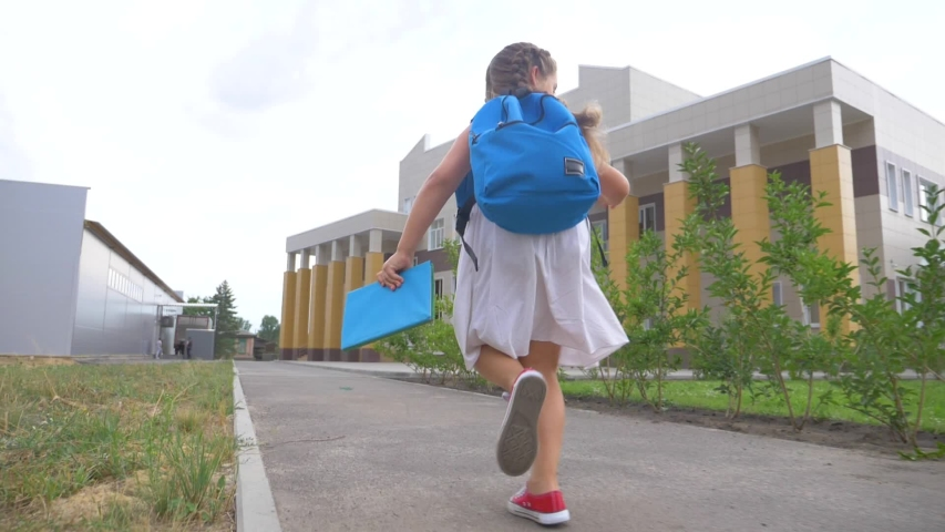 A little girl schoolgirl with a school backpack and a book runs through the park to school. Educated kids. Happy girl with a school backpack and a book rushes to school. Happy kids running to class | Shutterstock HD Video #1057043858