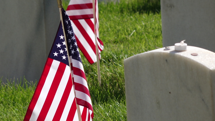 Zoom out from American flag to reveal many military headstones