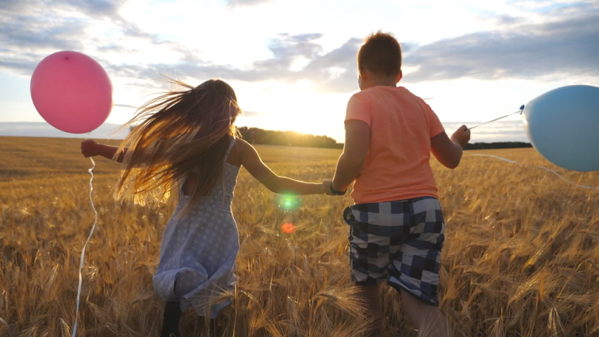 Couple of little kids with balloons running through wheat field, turning to camera and smiling. Small girl and boy holding hands of each other and jogging among barley meadow. Concept of child love   Shutterstock HD Video #1057045655