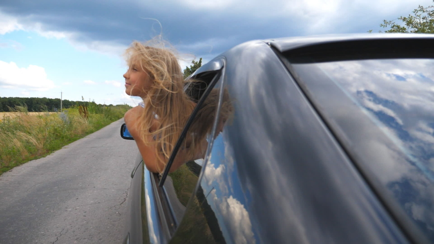 Beautiful small girl with long blonde hair leaning out of car window while riding through country road at overcast weather. Little kid looking out of open window moving auto and enjoying road trip