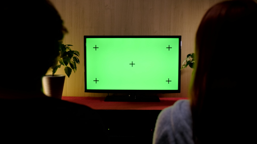 Couple Watches Green Mock-up Screen TV while Sitting on a Couch in the Living Room. | Shutterstock HD Video #1057046258