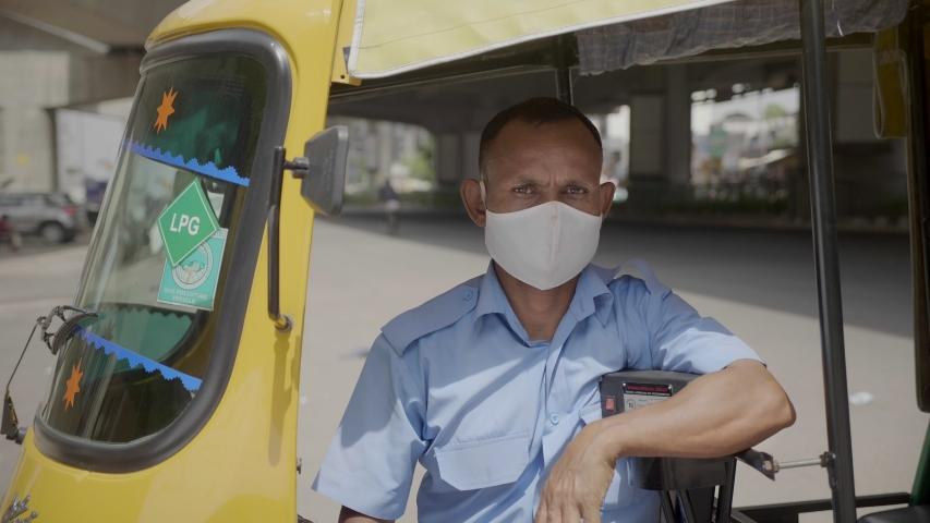 An Autorickshaw man sitting in a tuk tuk wearing face protective mask looking at the camera amid Coronavirus or COVID 19 epidemic or pandemic. Royalty-Free Stock Footage #1057060211