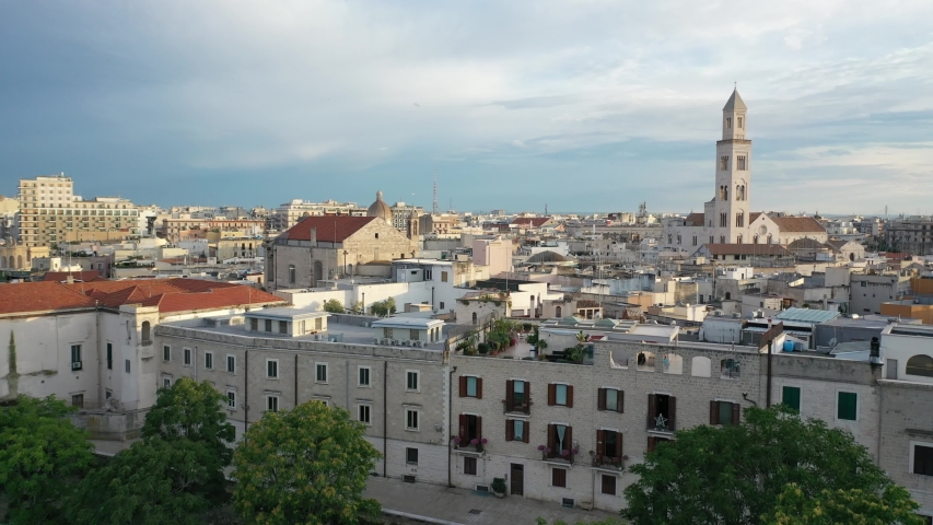 Beautiful panoramic aerial 4K video from flying drone at sunset to Bari old town ,Cathedral Saint Sabino ,San Nicola Basilica and Normanno Svevo Castle in summer evening. Bari ,Apulia, Italy (Series) | Shutterstock HD Video #1057067528