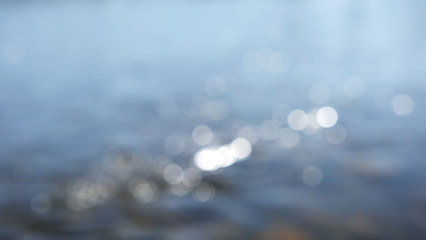 Bokeh sun glare reflected in the water surface. Sunrays flickering in the water stream. Abstract blurry out of focus bokeh background imagery. Slow motion.