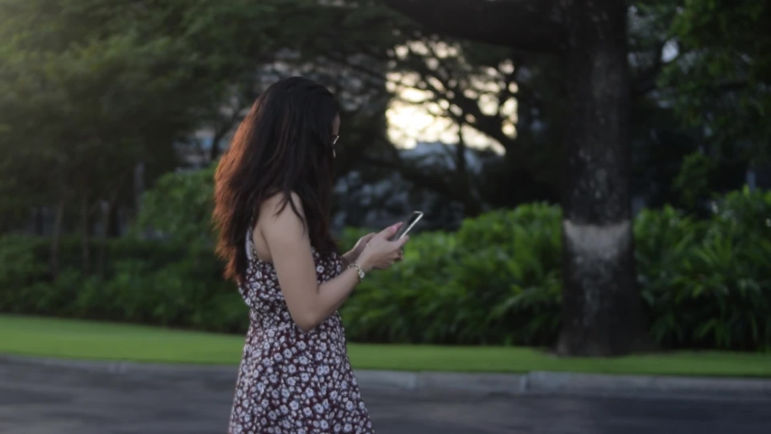 Asian woman using cell phone and walking on road, playing with hair