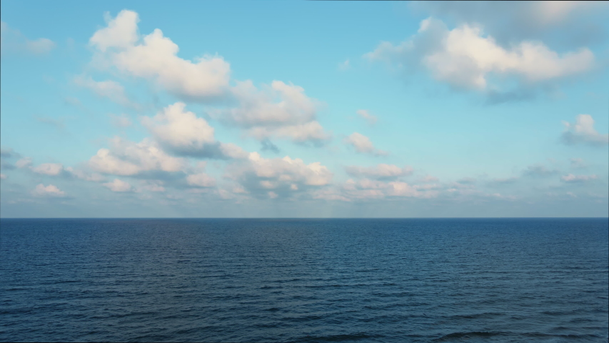 Blue sky with white clouds moving panorama summer. Sea in light of day aerial view of drone slide forward. Small waves on sea. Sunny sunset over the sea. Sun way. Horizon
