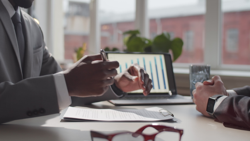 Midsection shot of afro-american entrepreneur in formalwear signing contract and giving handshake to male business partner while sitting together at office table Royalty-Free Stock Footage #1057081097