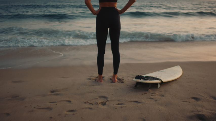 Surfer girl standing and looking at Pacific ocean, getting ready for a surfing training, camera moving in from back