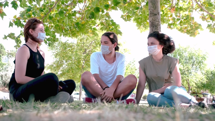 Young friends talking and laughing while sitting on grass. Meeting with friends in the public park during the coronavirus epidemic. Royalty-Free Stock Footage #1057094996