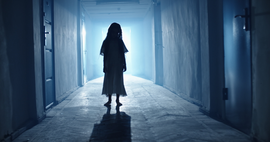 Little girl in white dress looking like a ghost slowly creeping down the hallway of a haunted house - halloween costume party, horror movie 4k footage   Shutterstock HD Video #1057101041
