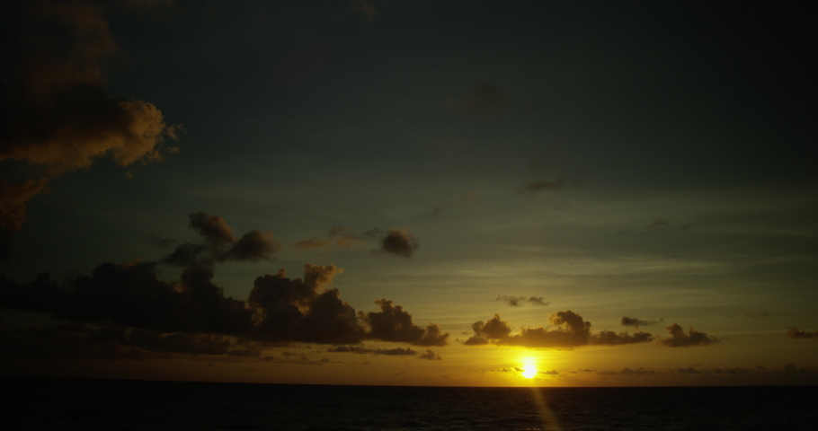 Sun slowly sets below the horizon at dusk with ocean in the foreground | Shutterstock HD Video #1057103063