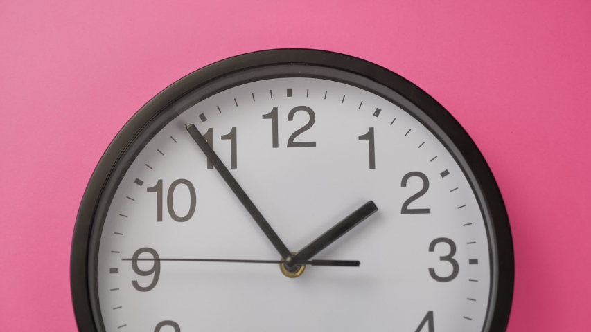Single white office clock hanging on a pink color wall