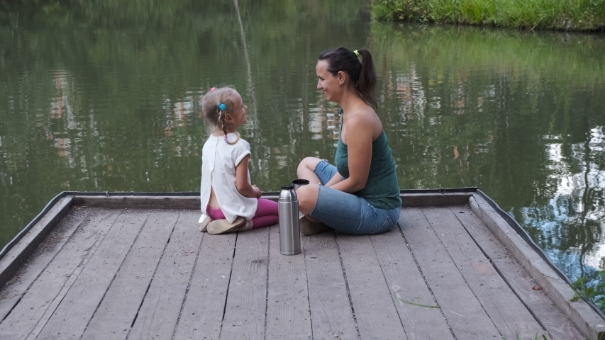 Happy Young Mother and her Cute Little 5-year old Daughter having Picnic while Sitting on the Wooden Pier by the Pond. Happy Childhood, Family Summer Activities and Lifestyle Concept