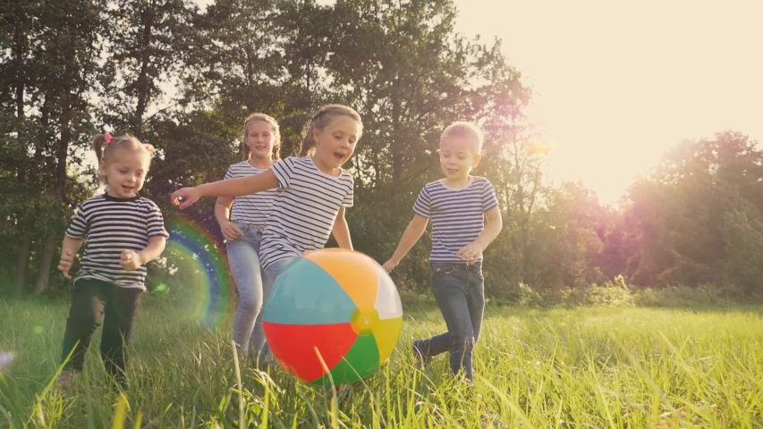 Happy family of children playing with a ball in park. Happy kid are run. Children run after ball in  park. Happy family of children at sunset in park, having fun playing with a ball. Kid dream team. Royalty-Free Stock Footage #1057108196