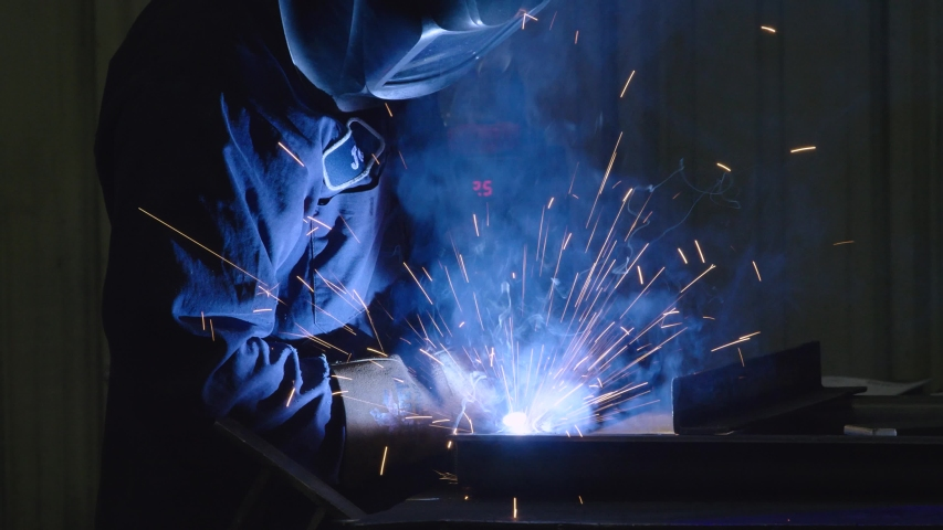 Dramatic shot of Man Welding in USA Factory Working with Steel in Classic Blue Collar American Job