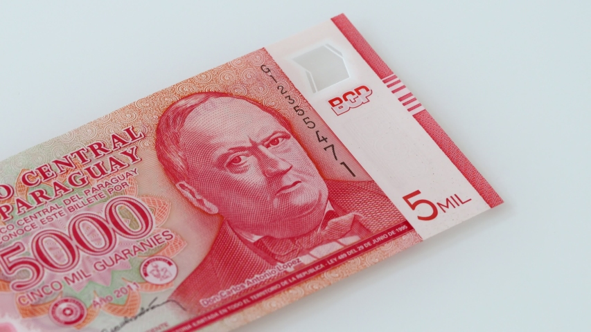 Paraguay money, Guaranies banknotes, thrown on the table one by one. White background