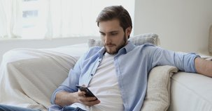 Handsome young european appearance man relaxing on comfortable couch, using mobile application in living room. Happy caucasian guy chatting in social network, dating online or web surfing internet.