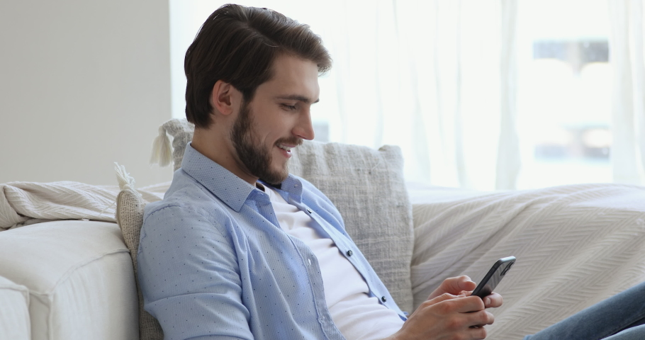 Side view happy young handsome guy sitting on sofa, using dating online mobile application indoors. Smiling man enjoying communicating with friends in social network or playing games on phone. Royalty-Free Stock Footage #1057121849