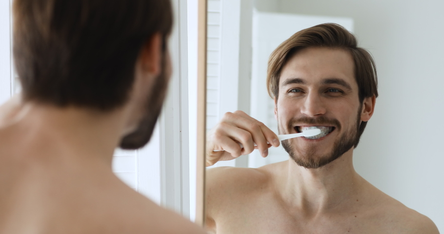 Close up head shot mirror reflection young happy bare man brushing teeth with toothbrush and toothpaste. Smiling handsome guy enjoying morning oral anti cavity hygienic routine alone in bathroom.