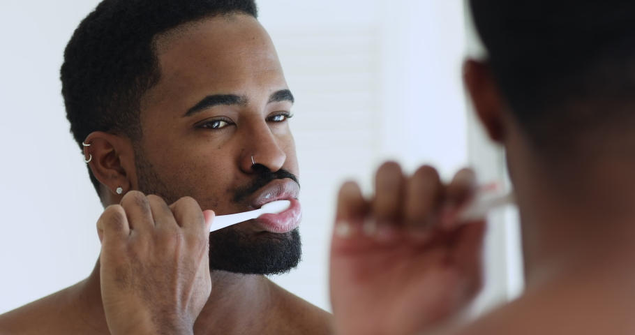 Close up head shot young handsome mixed race man brushing teeth in bathroom. Hipster african ethnicity guy looking in mirror, doing morning oral mouth hygienic daily procedure, toothcare concept. Royalty-Free Stock Footage #1057124996