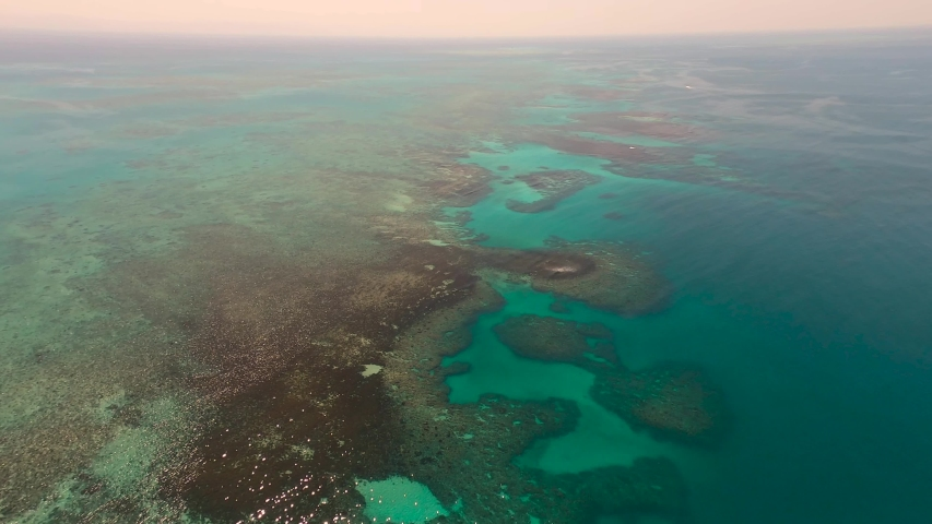 Great Barrier Reef Blue Sea view. Beautiful aqua & turquoise waters, with coral reef patterns in the ocean. View from helicopter, on vacation. Marine life, global warming, protection, island. 4K. | Shutterstock HD Video #1057127021