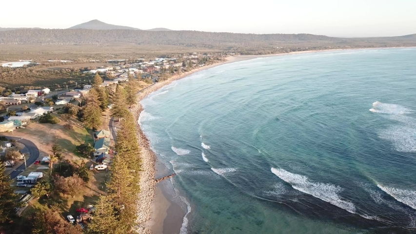 Aerial Drone Over Blue Ocean Waves And Beach Seaside Town With Mountain In The Distance In Australia | Shutterstock HD Video #1057128158