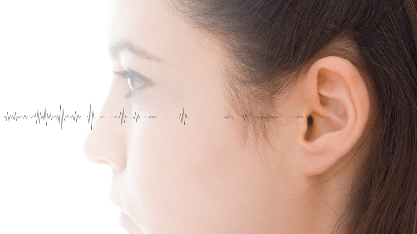 Hearing test showing ear of young woman with audio sound waves simulation technology - isolated on white loopable