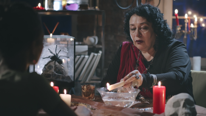 Back view of female client visiting old gypsy seer. Witch performing ritual with burning candle and bowl of water reading fortune of young woman customer | Shutterstock HD Video #1057132628