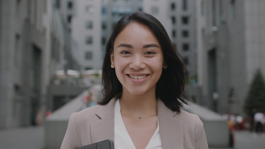 Smiling asian young woman in formal outfit looking to camera outside on street feel happy businesswoman portrait business beautiful modern manager pretty slow motion Royalty-Free Stock Footage #1057134581