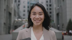 Smiling asian young woman in formal outfit looking to camera outside on street feel happy businesswoman portrait business beautiful modern manager pretty slow motion