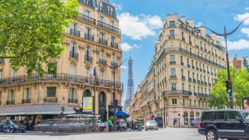 Romantic cozy view of the famous Eiffel tower from a small paris street on a cloudy sunny day in spring summer - wide horizontal panorama, traffic in motion blur.Camera fixed position | Shutterstock HD Video #1057141151