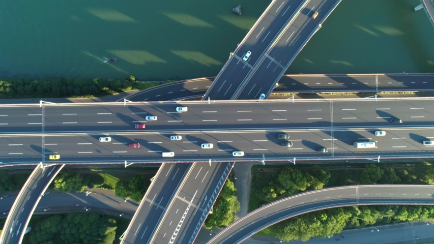 Aerial drone view of highway multi-level junction road with moving car at sunset. Active movement of transport cars vehicles in different directions.The concept of the urban. China. Top down view.