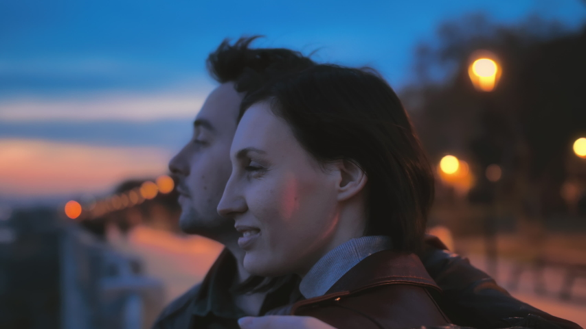 Close-up portrait of a beautiful young couple on the street of the night city against the background of colorful lights. Love story, romantic atmosphere. Two lovers hug and watch the sunset. Slow   Shutterstock HD Video #1057146251