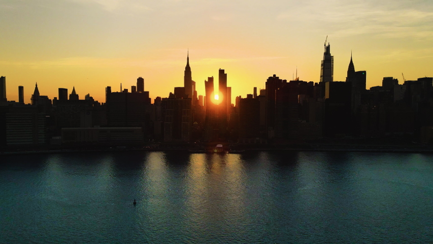 Skyscrapers' Silhouette, aerial sliding shoot of New York City at golden hour, with the Sun crossing the city from one side to another. | Shutterstock HD Video #1057146548