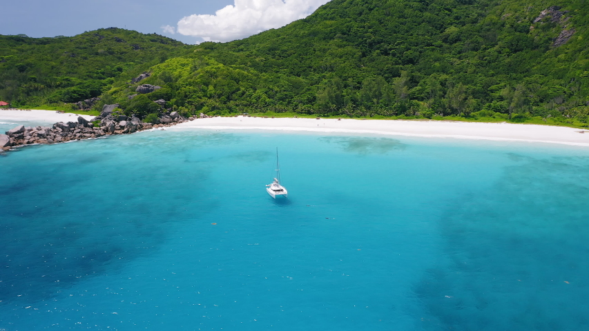 Aerial view footage of luxury catamaran yacht moored in clear turquoise blue ocean water of Petite Anse sandy beach of La Digue island, Seychelles. Travel concept. | Shutterstock HD Video #1057147757