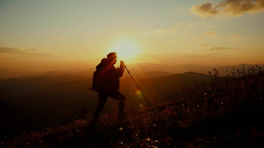 Epic shot of a woman hiking on the edge of the mountain in beautiful sunset. Camera follows hipster millennial young woman running up on top of mountain summit at sunset Royalty-Free Stock Footage #1057147976
