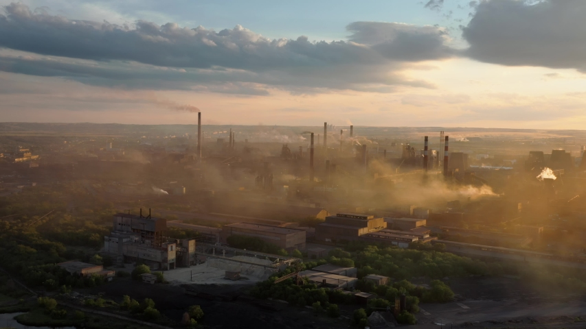 Drone shot of industrial zone with thick smog and burning fossil fuels. Zoom in aerial shot of factory zone shot from top, air pollution and soot in many factory chimneys in city area Royalty-Free Stock Footage #1057148015