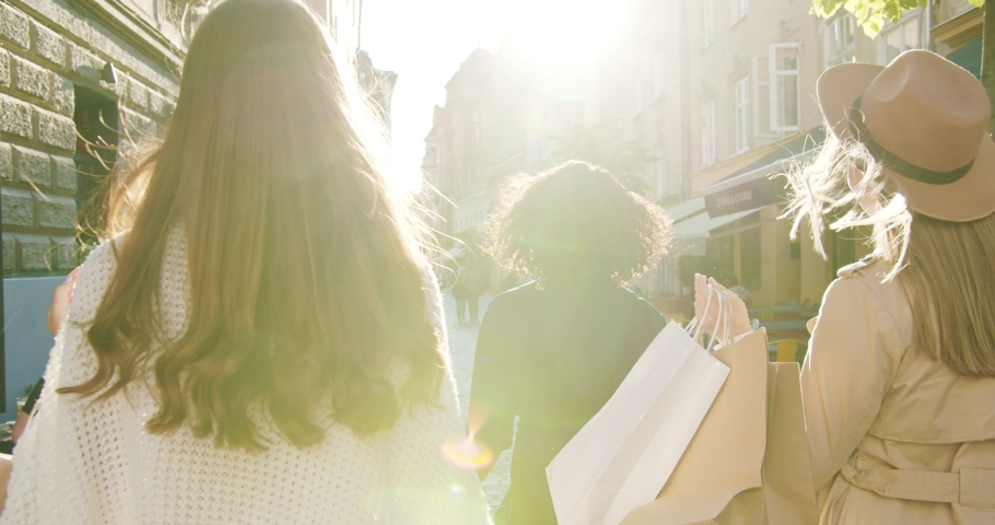 Pretty multi-ethnic women in sunshine outdoors. Beautiful Caucasian girl in hat walking on street in city. African American female walks in town and holds shopping bags. Buyer, urban concept Royalty-Free Stock Footage #1057151621