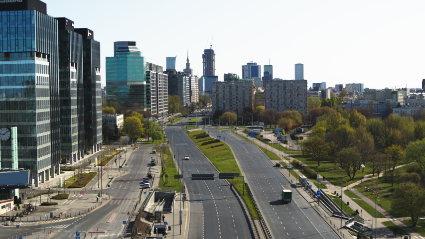 Empty street in Warsaw city, Poland aerial view. Quarantined city, empty abandoned streets during corona virus outbreak. Drone shot flying over buildings, parked cars and street COVID Royalty-Free Stock Footage #1057153046