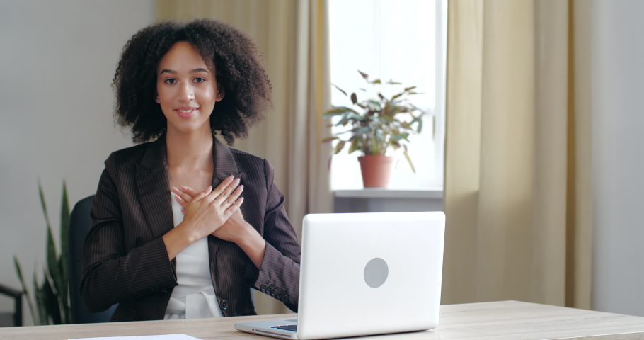 Curly smiled millennial business woman sitting at office home table, put folded palms on heart, keeps his hands on chest. Concept of trust, symbol friendly, signe gratitude, believe and charity Royalty-Free Stock Footage #1057157572