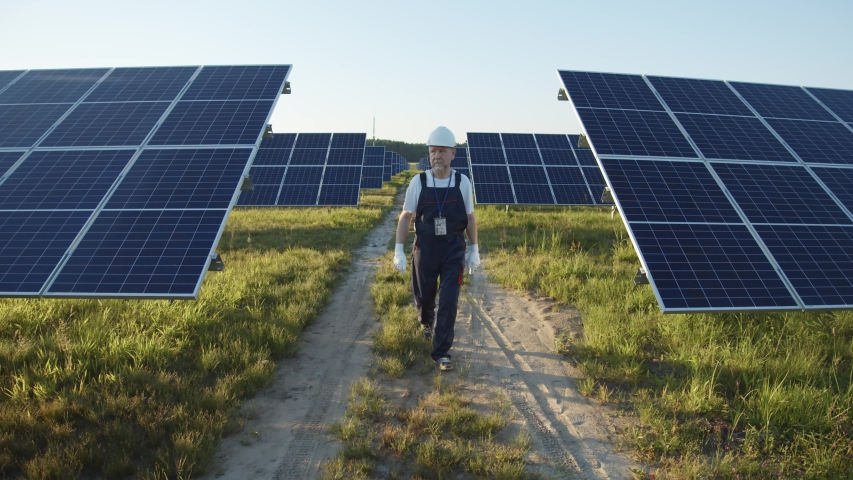 Professional mature man technician in hardhat walks on new ecological solar construction outdoors. Farm of solar panels. Concept of electricity, ecology, technologies. Royalty-Free Stock Footage #1057160278