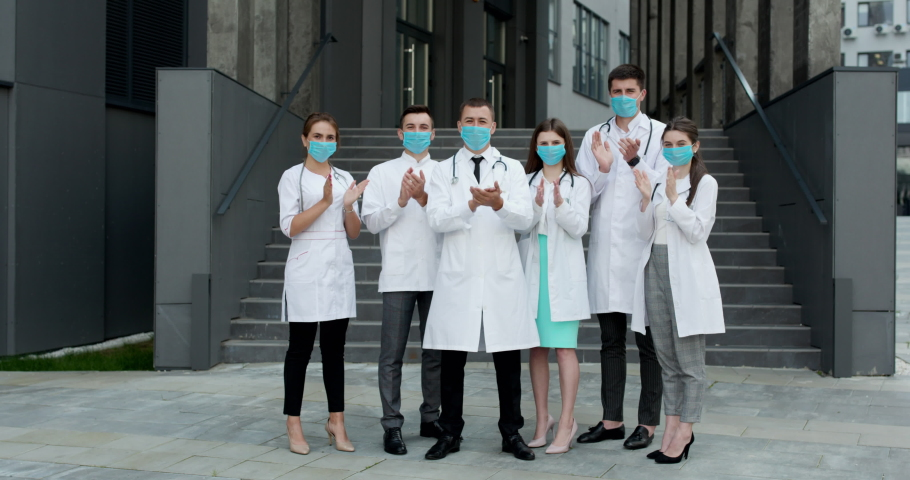 Medical staff from the hospital who are fighting coronavirus applaud back the people and police officers for their support. Group of doctors with face masks. Corona Virus and Healthcare Concept. Royalty-Free Stock Footage #1057160656