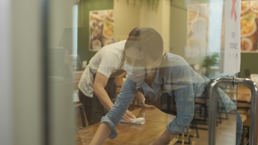 Waiter wearing protective face mask while cleaning tables in restaurant Royalty-Free Stock Footage #1057167955