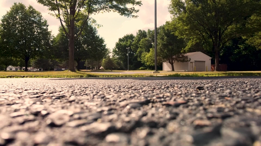Flat angle of a blacktop parking lot. Filmed in summer in a suburban neighborhood near Detroit, Michigan. Sepia like tones highlighted.