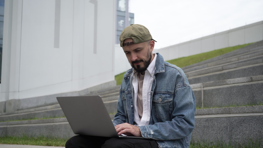 Bearded male it worker sits in an urban city environment on a stone bench with a computer. Man freelance programmer working on laptop developing new products for a technology company. Outdoor office. | Shutterstock HD Video #1057175572